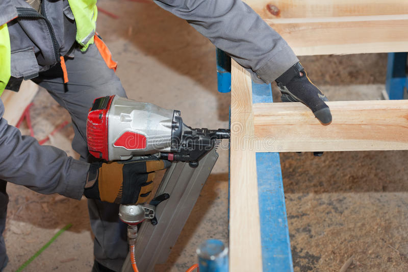 Building a wall for frame house.Worker use Framing Nailer to attach wooden beams. Building a wall for frame house.Worker use Framing Nailer to attach wooden stock images