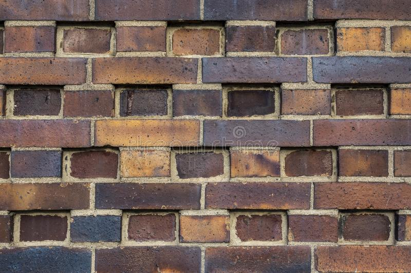 Building wall made of dark, yellow to brownish clinker bricks with various alternating patterns. The stones are offset in rows,. Turned, indented or omitted stock images
