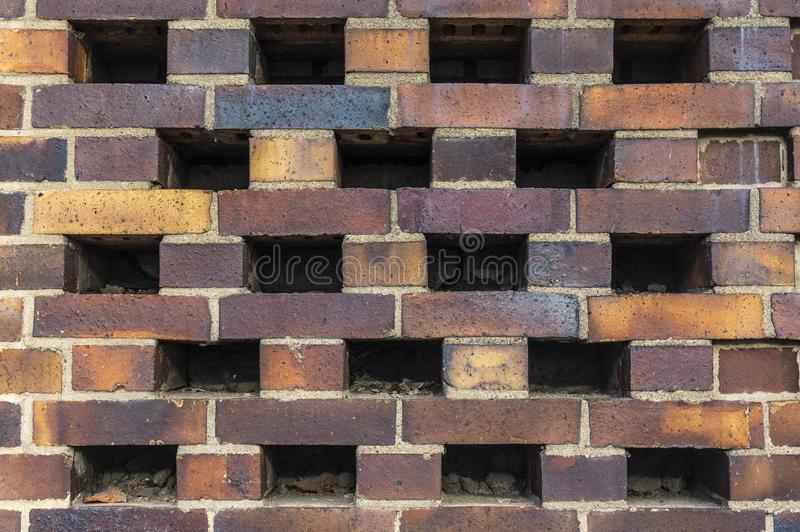 Building wall made of dark, yellow to brownish clinker bricks with various alternating patterns. The stones are offset in rows,. Turned, indented or omitted for royalty free stock photography