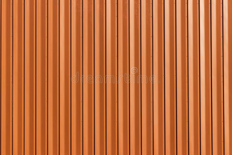 Building with wall of orange metal. Corrugated texture, galvanized steel surface. Abstract architectural pattern for background stock images