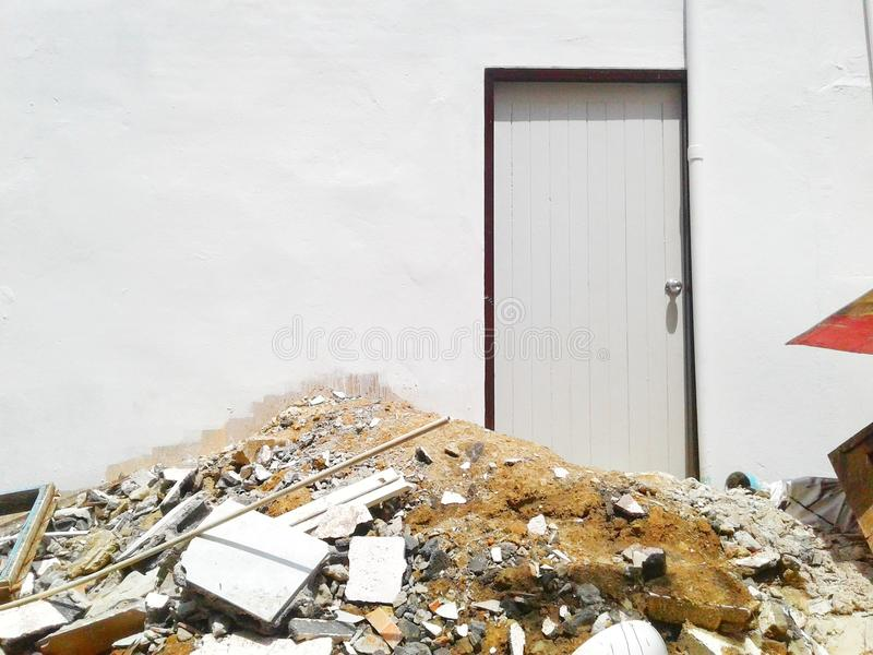 The building was demolished. By a front pile of building materials and a wall behind the house with doors stock image