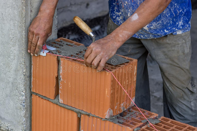 Building worker setting string line between clay block stock image