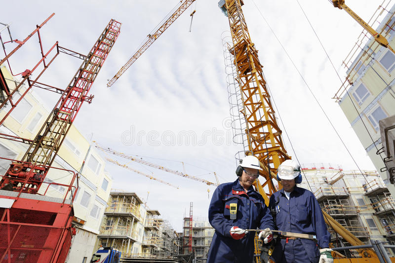 Building workers and construction industry. Two construction workers with large industry in background, cranes and scaffolding, wide-angle view stock images