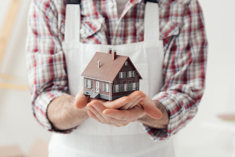 Building your house. Building contractor holding a model house: construction, renovation and real estate concept royalty free stock photos