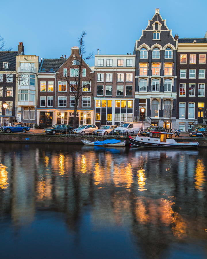 Buildings along the Amsterdam Canals at twilight. AMSTERDAM, NETHERLANDS - 16TH FEBRUARY 2016: A view along the Amsterdam Canals at twilight. Buildings, people royalty free stock image