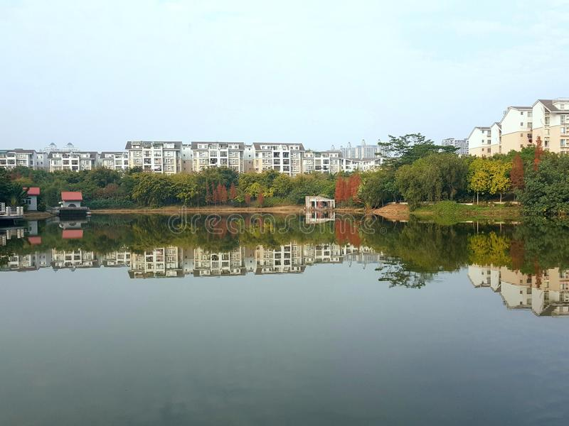 The buildings along the lake and their reflections form a belt. The long buildings along the lake and their reflections form a belt stock images