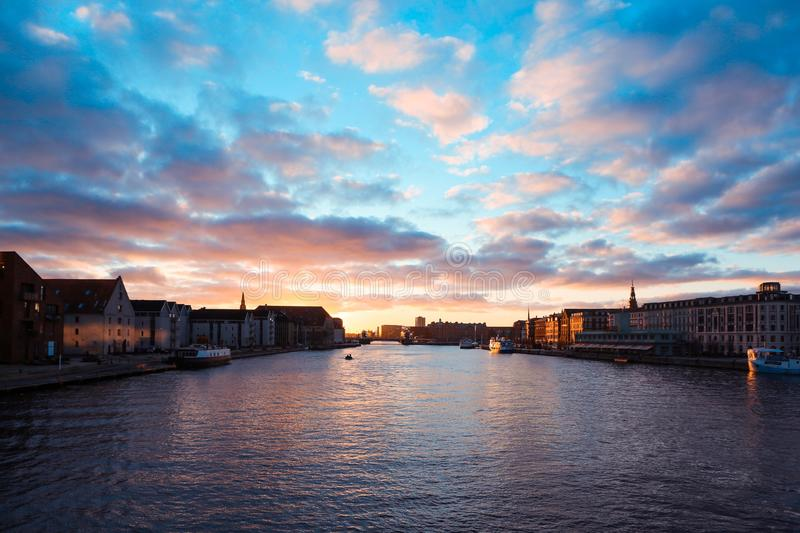 Buildings by the body of water under a pinkish sky with clouds during sunset in Copenhagen, Denmark. A wide shot of buildings by the body of water under a royalty free stock images