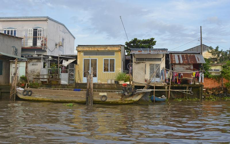 Buildings on Can Tho Waterway. Can Tho, Vietnam - December 31st 2017. An old wooden boat moored next to three small houses which look out onto a waterway near royalty free stock image