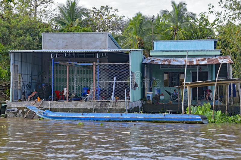 Buildings on Can Tho Waterway. Can Tho, Vietnam - December 31st 2017. Two woman sit and relax at back of their house which looks out onto a waterway in the royalty free stock photo