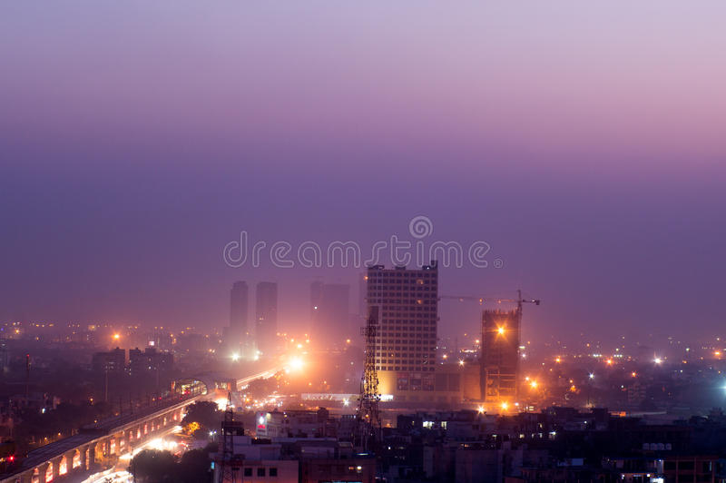 Buildings at dusk in Noida India. Noida, India - 16th Nov 2016: Buildings in Noida at dusk with the lights shining bright. The cityscape of noida is now being stock image