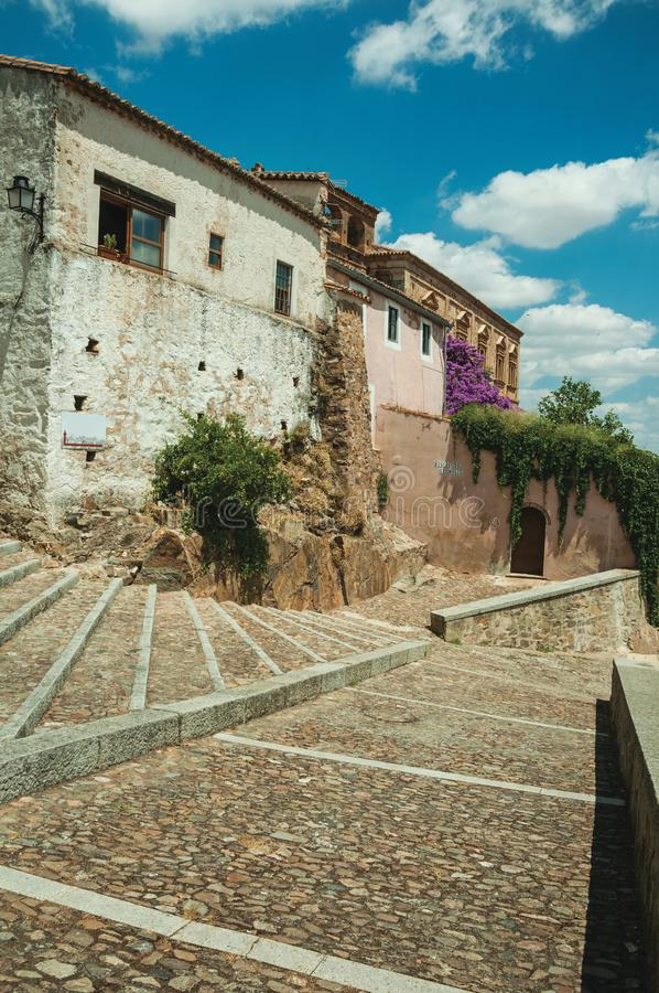 Buildings and flowering trees over a stairway with cobblestone at Caceres royalty free stock images