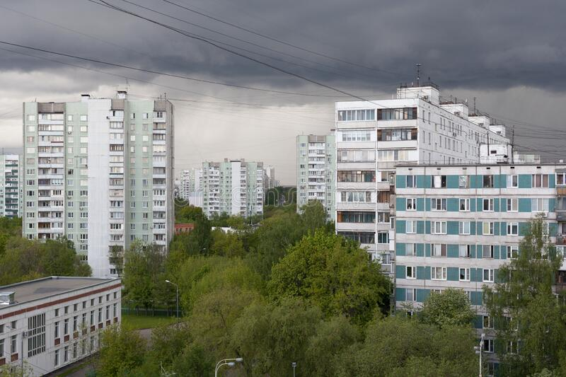 Buildings and green trees against stormy sky on spring day stock photos