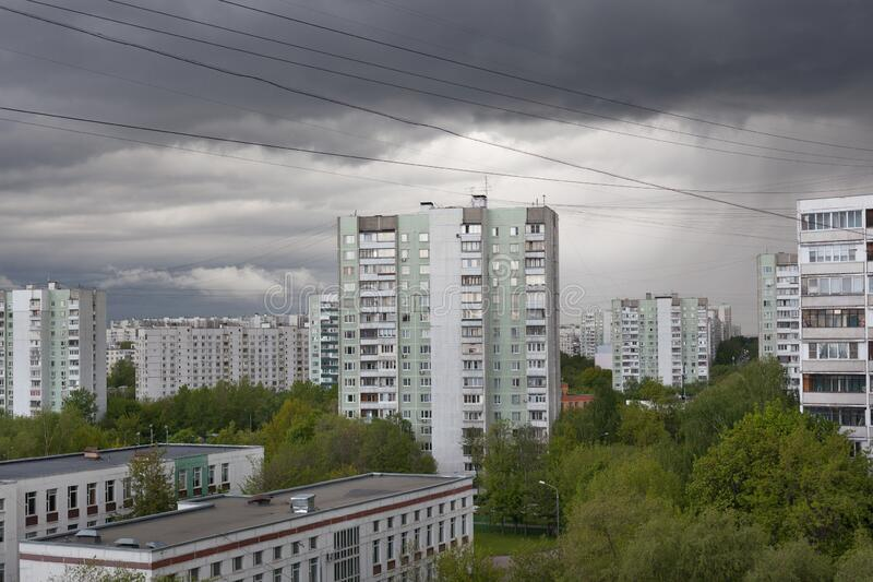 Buildings and green trees against stormy sky on spring day royalty free stock photography