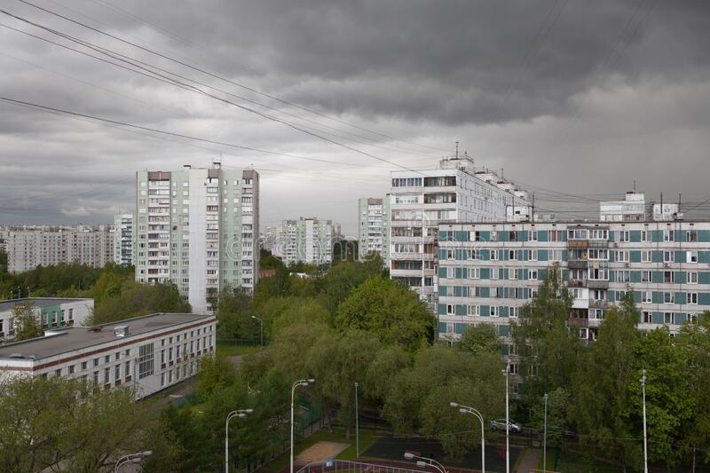 Buildings and green trees against stormy sky on spring day stock photo