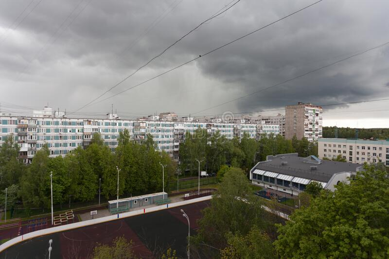 Buildings and green trees against stormy sky on spring day stock image