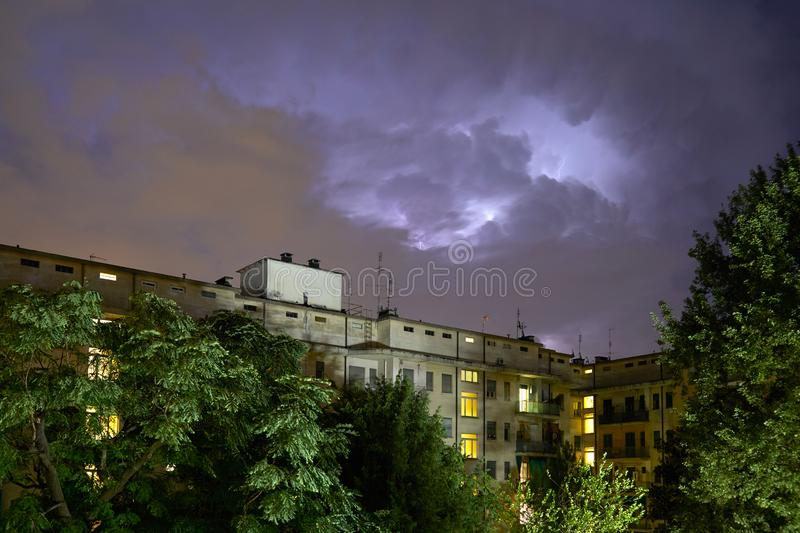 Buildings and green trees at night, illuminated sky during a lightning storm stock photography