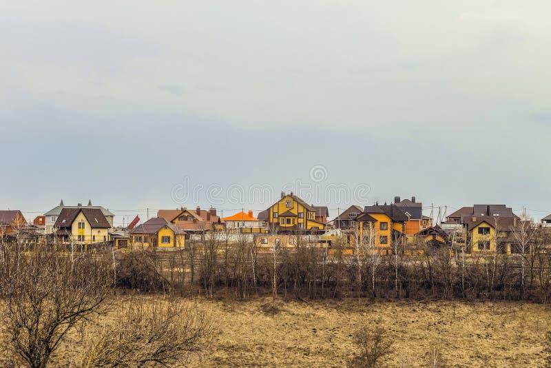 Buildings individual suburban housing in early spring. Belgorod Region, Russia. Suburban skyline. Buildings individual suburban housing in early spring stock photo