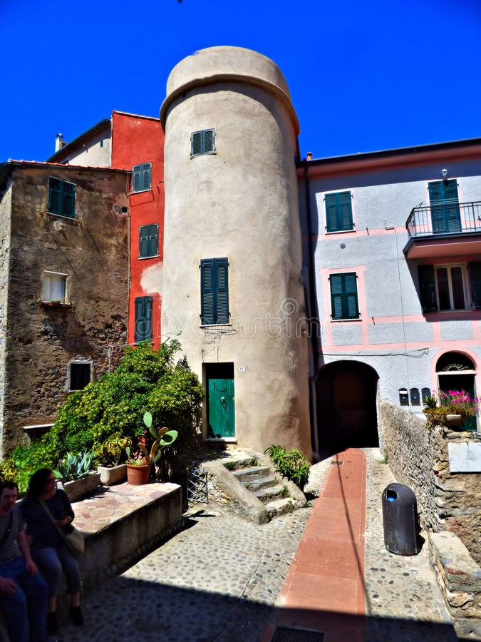 Buildings in Lerici Italy on the Gulf of La Spezia. Buildings in Lerici Italy of different architectural style with a blue sky background. Ted cobblestone leads stock image