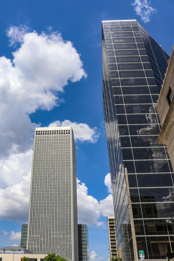 Buildings of modern city jutting up into intensely blue clouded sky with reflections.  stock images