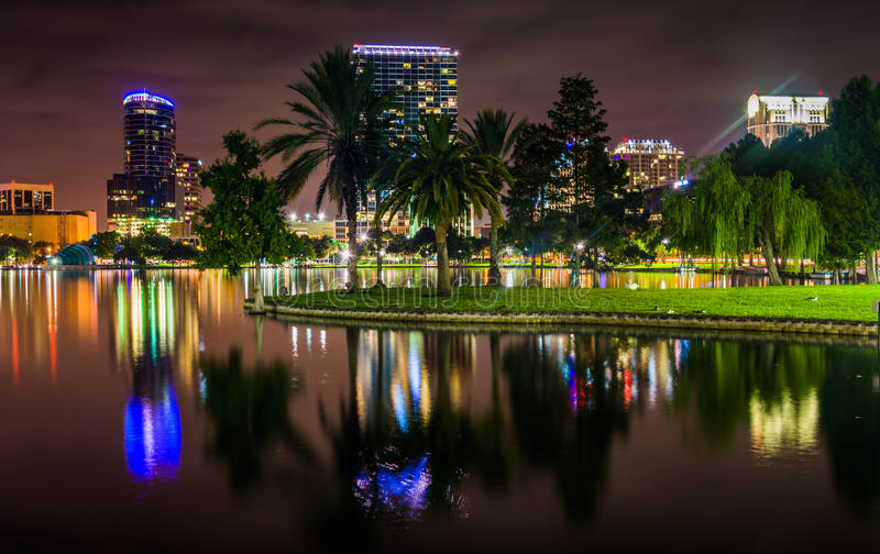 Buildings and palm trees reflecting in Lake Eola at night, Orlando, Florida. stock photos