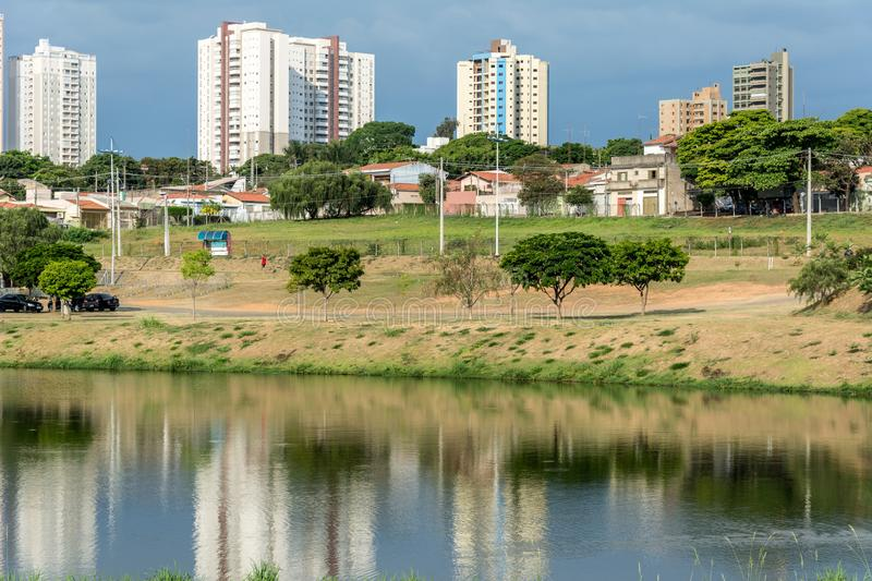 Buildings reflected on the water of a river, in the Ecological Park, in Indaiatuba, Brazil. 2019, october; Indaiatuba, Brazil. Buildings reflected on the water royalty free stock photo