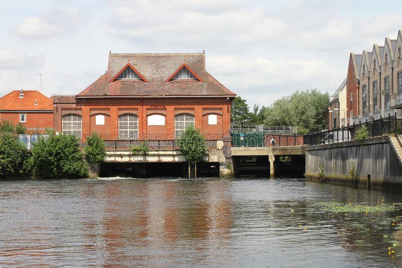 Buildings on River Yare in Norwich. With water and trees and red brick buildings stock image