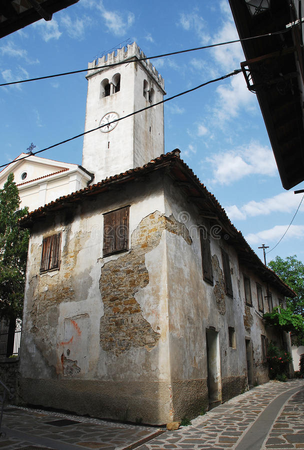 Buildings in Smartno. An old historic, yet rather delapidated building in the historic Slovenian town of Smartno in the Goriska Brda area with a church bell stock images