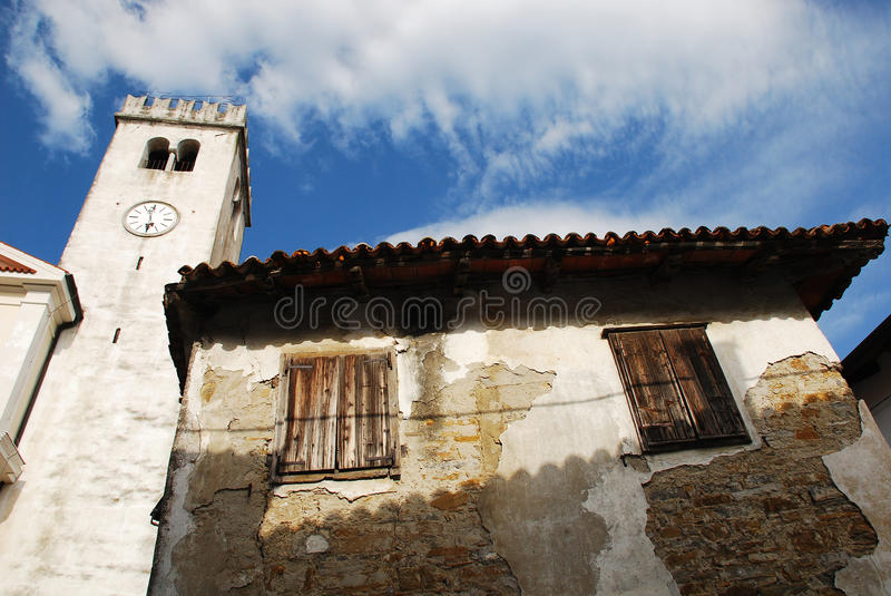 Buildings in Smartno. An old historic, yet rather delapidated building in the historic Slovenian town of Smartno in the Goriska Brda area with a church bell stock photography