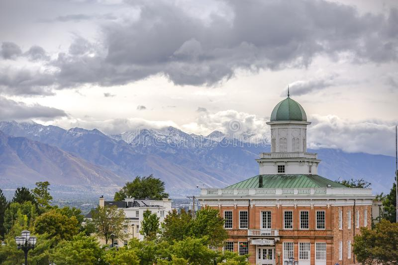 Buildings and snow capped mountain under clouds. Buildings and trees with a majestic snow capped mountain in the background. Scenic view in Salt Lake City with royalty free stock photos