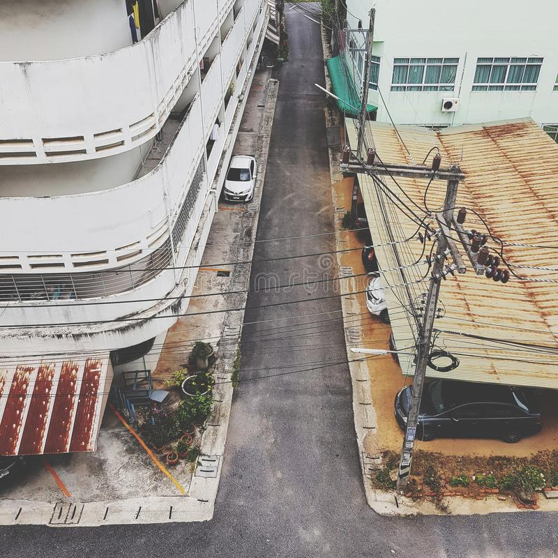 Buildings and street scene in city. Cityscape, town, townscape, view, street-photography, house, parking, rooftop, road, vehicle, architecture, asia, thailand royalty free stock photography