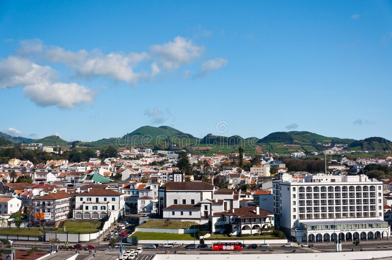Buildings surrounded by hills covered in greenery in The Port of Ponta Delgada in Portugal. The buildings surrounded by hills covered in greenery in The Port of royalty free stock photo