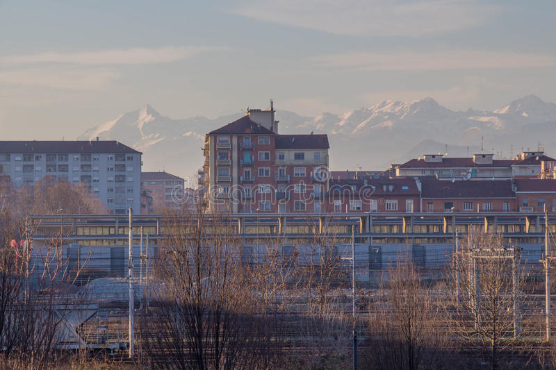 Buildings and white mountains on background. Lingotto district. Turin. Italy. royalty free stock photography