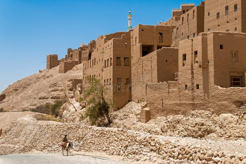 Buildings in Yemen. A man rides his donkey in front of buildings made from mud and stone on May 8, 2007 in Al Hajarayn, Yemen. Among other arabic countries, in stock images