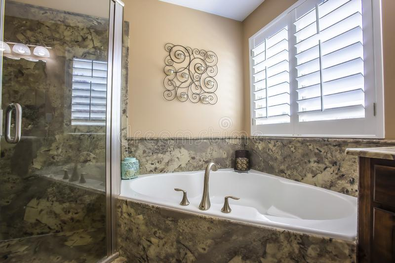 Built in bathtub at the corner of a bathroom with wall decor and window stock images