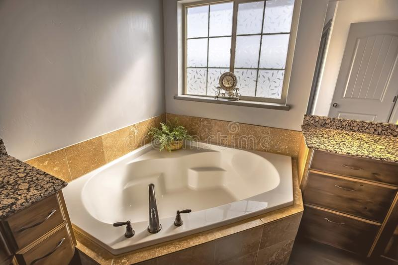 Built in bathtub at the corner of a sunlit bathroom with frosted glass window stock photography