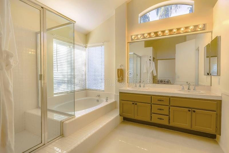 Built in bathtub and shower with glass door inside a beautiful bathroom. Vanity unit with double sink, large mirror, bright lights, and wood cabinets can also royalty free stock image