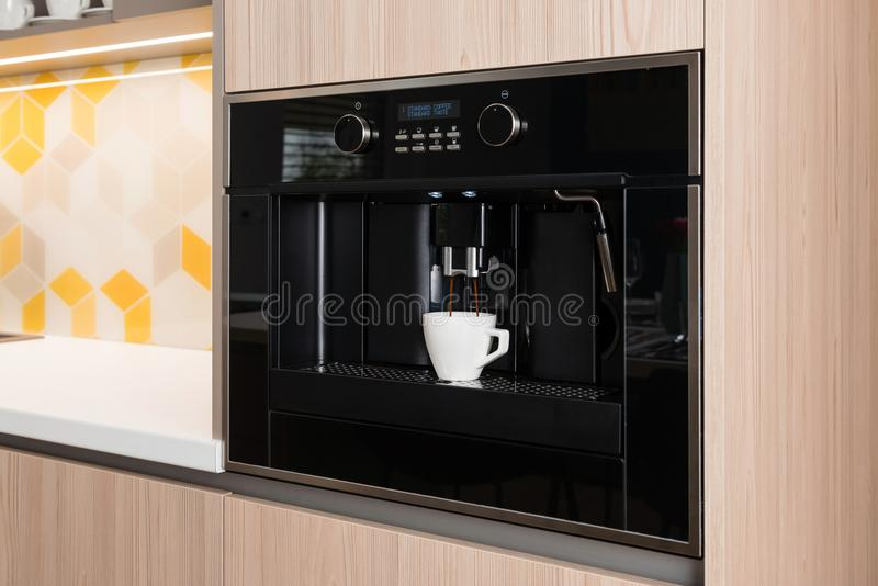 Built-in coffee machine in kitchen. Built-in coffee machine in contemporary kitchen royalty free stock image