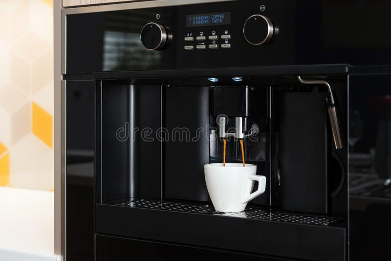 Built-in coffee machine making coffee. Detail of built-in coffee machine in contemporary kitchen royalty free stock image