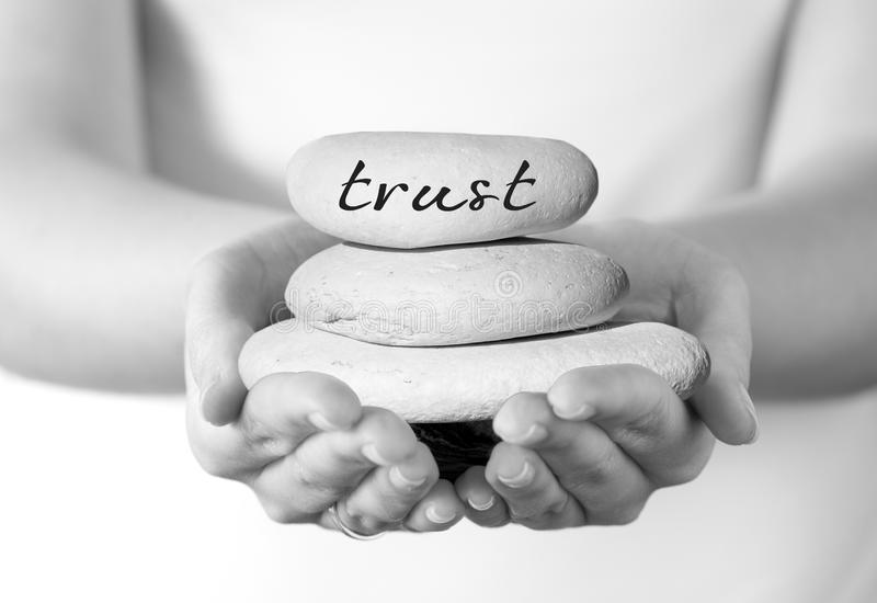Built on Trust. Concept. Hands holding a small stack of pebbles with 'Trust' written on the top stone royalty free stock photo