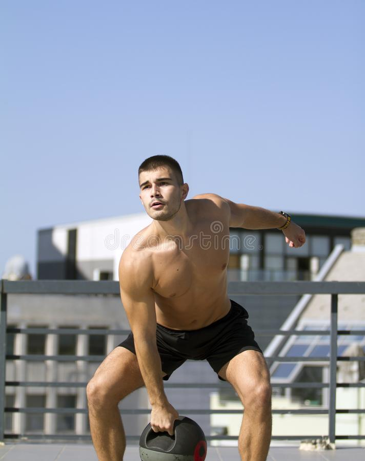 Built young sportsman. Exercise with a Grip Medicine Ball. royalty free stock images