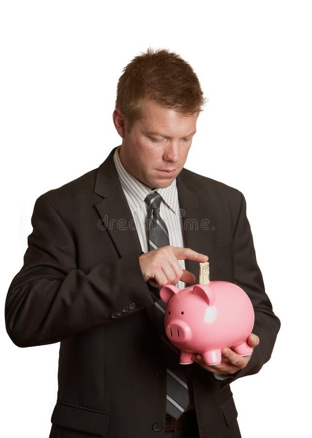 Buisinessman que conserva o banco piggy imagem de stock