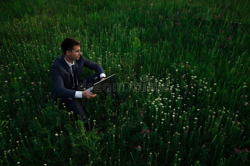 Buisnessman con il computer portatile si siede sull'erba immagine stock