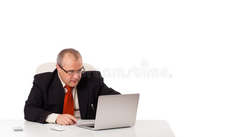 Buisnessman, das am Schreibtisch sitzt und Laptop mit Kopienraum schaut stockbilder