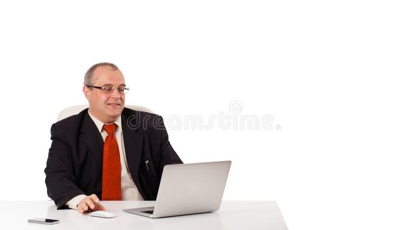 Buisnessman, das am Schreibtisch sitzt und Laptop mit Kopienraum schaut lizenzfreies stockbild