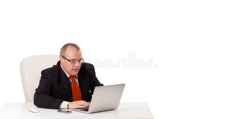 Buisnessman, das am Schreibtisch sitzt und Laptop mit Kopienraum schaut stockbild