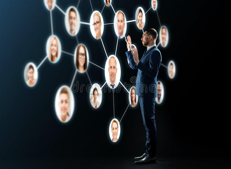 Buisnessman looking at contacts network. Business, people, corporate, headhunting and technology concept - buisnessman in suit looking at contacts network over stock photos