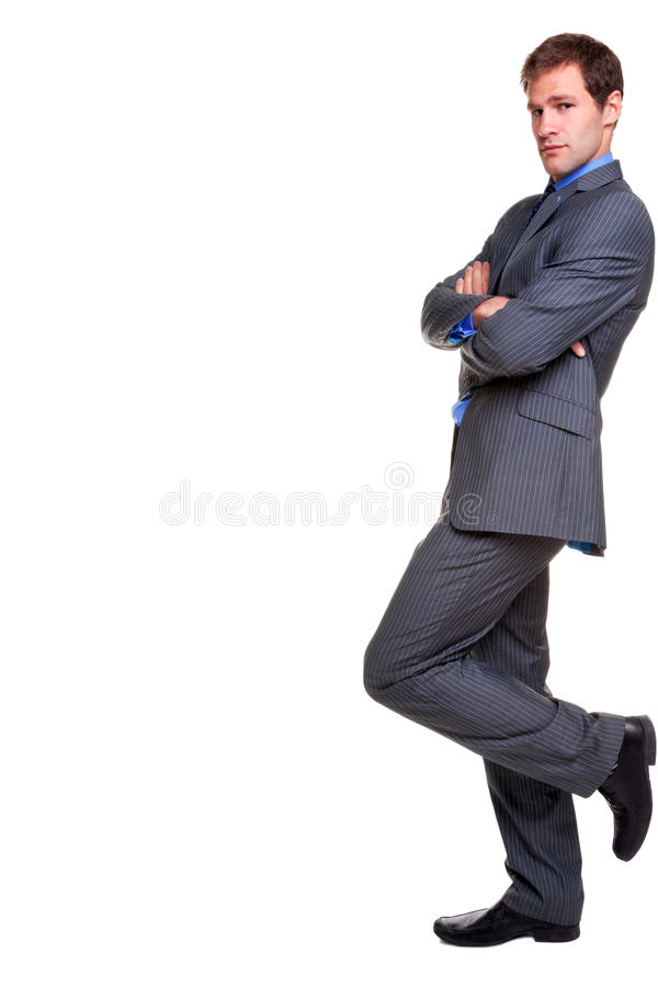 Buisnessman pinstripe suit leaning isolated. Businessman in a pinstripe suit leaning with his arms folded, looking at camera, isolated on a white background royalty free stock photography