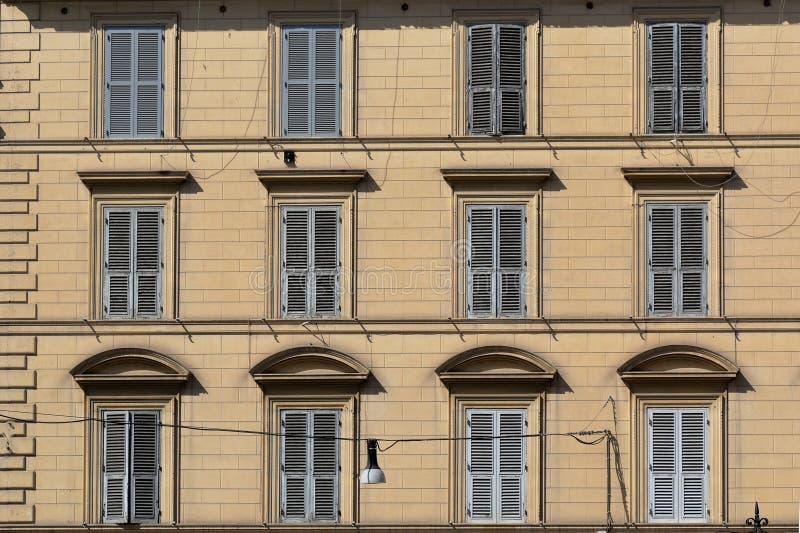 Buiten gele muur van de oude bouw met vensters en blinden royalty-vrije stock afbeelding