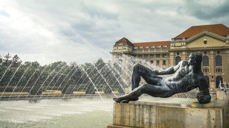 Buiten het belangrijkste buidling van de Universiteit van Debrecen met Fontein en Standbeelden stock fotografie