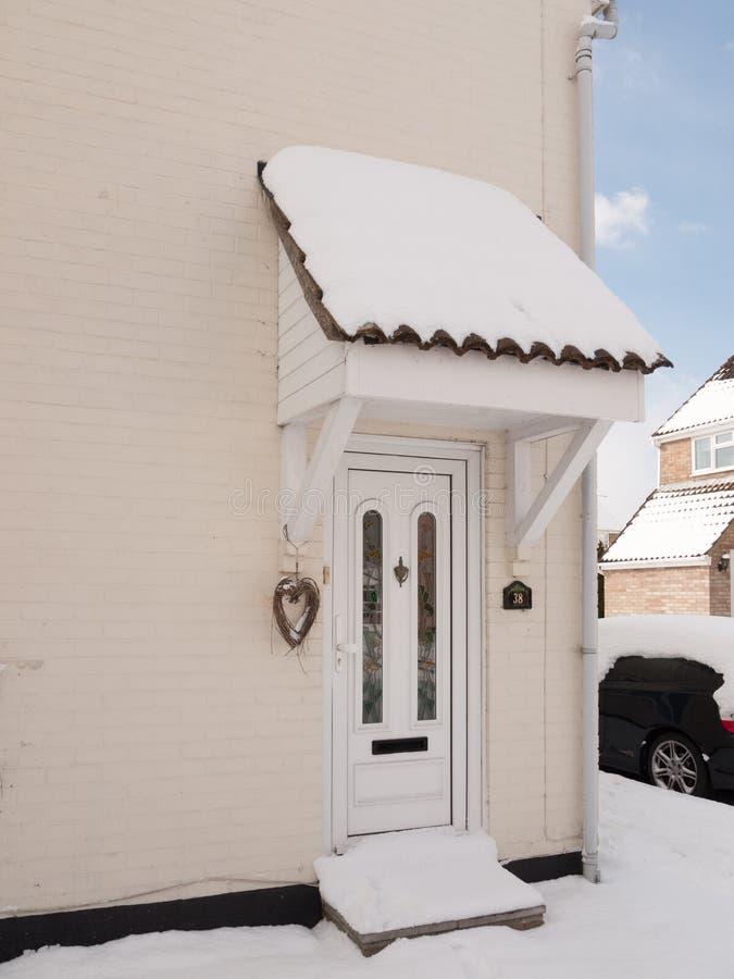 Buiten huis met sneeuw op voor behandelde portiek royalty-vrije stock afbeelding